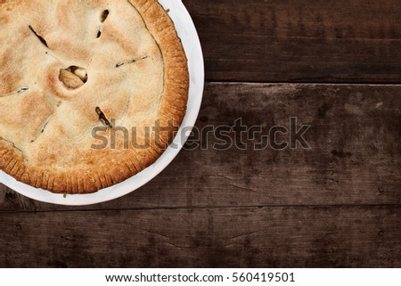 Homemade apple pie dessert shot from overhead over a white wooden table top with room for copy space.
