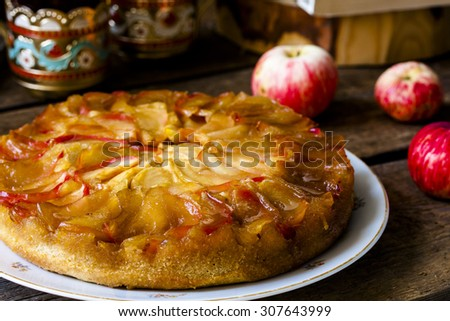 Homemade apple pie with cinnamon and caramel on wooden background - stock photo