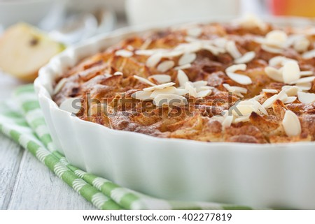 Homemade apple pie with in a white baking form on a white wooden background, closeup, selective focus - stock photo