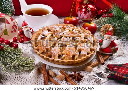 homemade apple pie with raisins,cinnamon and anise star on white plate for christmas time