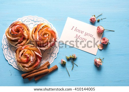 Homemade Apple rose cake with sugar powder on blue  wooden background. Top view.  Handmade gift for mom/ Mothers day concept card. - stock photo