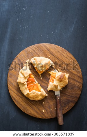 Homemade apricot pie on the wooden cutting board. Chalkboard background with copy space - stock photo