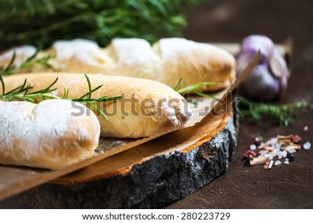Homemade baguette with Rosemary on rustic wooden background - stock photo