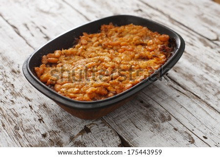 Homemade baked beans in a clay pot arranged on rustic wooden white table. - stock photo