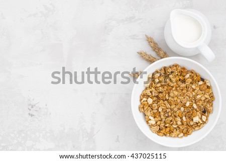 homemade baked muesli and milk on white background, top view, horizontal
