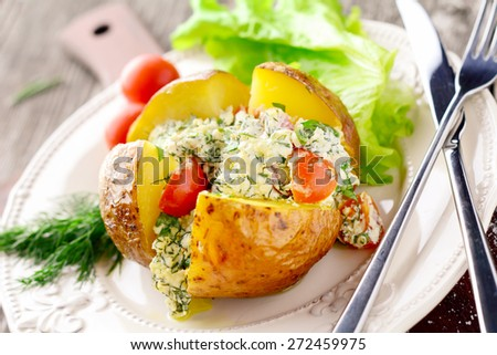 Homemade baked potato stuffed with cottage cheese, cheese, herbs and tomatoes on white plate. Served with fresh tomatoes and green salad leaf. Angle view - stock photo