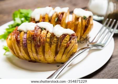 Homemade baked potato with bacon and herbs - stock photo