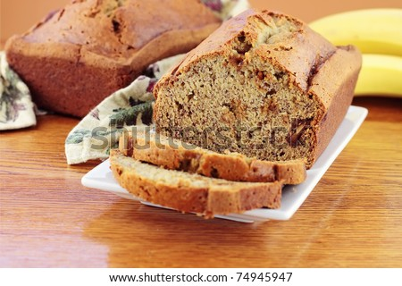 Homemade banana bread with fresh bananas. Extreme shallow DOF with selective focus on center on banana bread. - stock photo