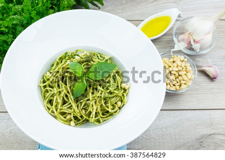 Homemade basil pasta with green pesto in wide brim bowl on wooden table with bowls of cheese, garlic, olive oil and cilantro - stock photo
