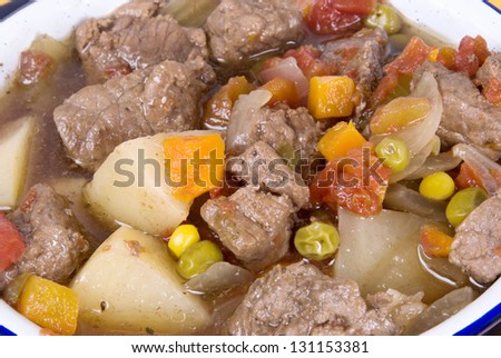 homemade beef  and vegetable soup made with potatoes, celery, onions, herbs and spices, carrots, mixed vegetables, diced tomatoes, beef stew meat, low sodium beef broth, a bay leaf and garlic. - stock photo