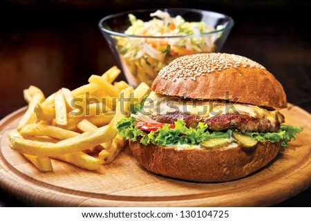 Homemade Beef burger. Beef, cheese, tomatoes, onion, green salad, tabasco sauce and french fries - stock photo