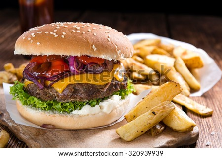 Homemade Beef Burger with Cheese and Chips on wooden background - stock photo