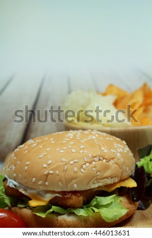 Homemade Beef Hamburger with fresh vegetables, Tomatoes, Lettuce, Cheese and Crispy Baked Sweet Potato Chips with Mild Paprika on Wooden background & the Evening Light for Food and Drink Theme.