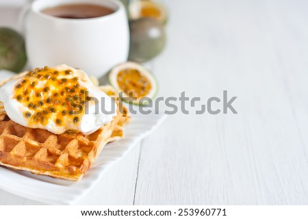 Homemade belgian waffles with cream and passionfruit pulp. Selective focus. Copyspace background. - stock photo