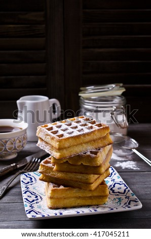 Homemade Belgian waffles with powdered sugar on a wooden background. Selective focus. - stock photo