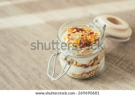 Homemade bircher muesli with toasted rolled oats, dried fruits, nuts, honey and fresh yogurt in a jar, traditional Switzerland breakfast meal, selective focus - stock photo