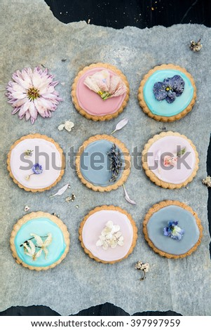 Homemade Biscuits covered with Pastel Color Icing and Spring Flowers on Dark background - stock photo