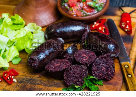 Homemade blood sausage prieta de sangre with tomato sauce salsa, lettuce on wooden board - stock photo