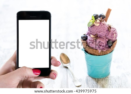 Homemade blueberries ice cream in coconut,selective focus and empty space on phone - stock photo