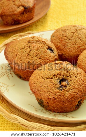 Homemade blueberry bran muffins in vertical format with selective focus and shot in natural light