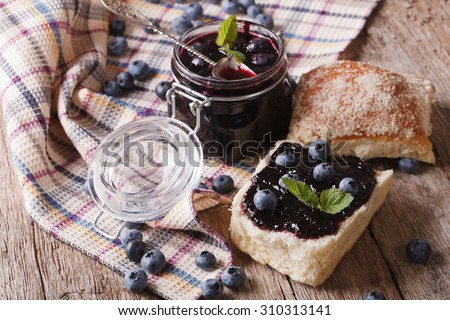 homemade blueberry jam and sweet bun close-up on the table. horizontal - stock photo