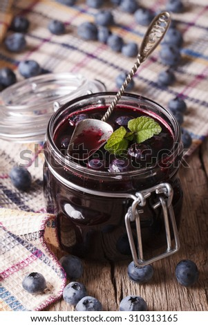 homemade blueberry jam in a glass jar close up on the table. vertical - stock photo