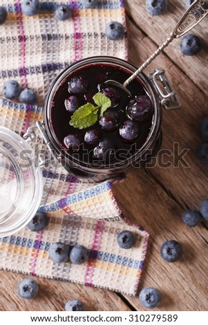 homemade blueberry jam in a glass jar on the table. vertical top view - stock photo