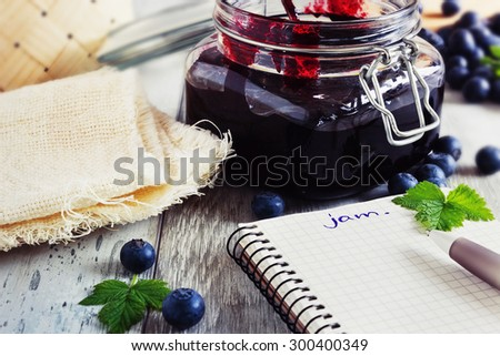 homemade blueberry jam in a jar and fresh blueberries on a table. a place for inscriptions. toning vintage style.health and diet concept. selective focus - stock photo