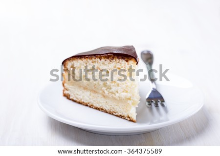 Homemade boston cream pie, piece of cake  filled with a custard and frosted with chocolate - stock photo