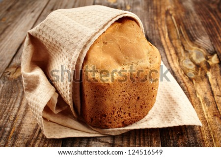 Homemade bread in a towel on a wooden board