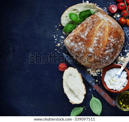 Homemade bread loaf and fresh ingredients for making sandwiches (tomatoes, basil, olive oil, cream cheese) on rustic dark background. Cooking, Healthy or vegetarian eating concept. - stock photo