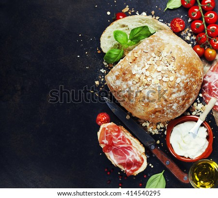 Homemade bread loaf and fresh ingredients for making sandwiches (tomatoes, basil, olive oil, cream cheese) on rustic dark background. Background layout with free text space. - stock photo