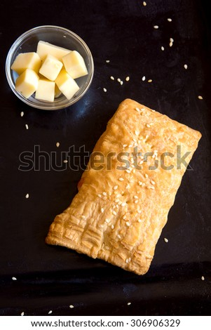 Homemade bread puff with goat cheese and sesame seeds over black pan - stock photo