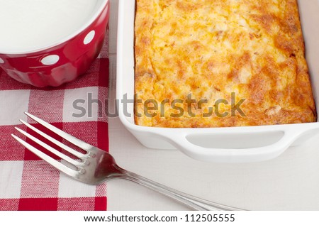 Homemade breakfast casserole with cup of milk
