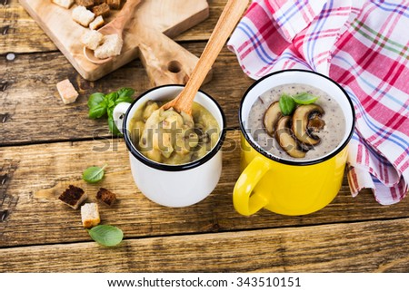Homemade brown lentil soup with chickpeas and  mushroom soup with fried mushrooms  in mug on wooden rustic table, winter vegetarian food concept - stock photo