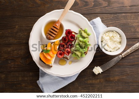 Homemade Bruschetta with fresh fruit - apricots, cherries, kiwi, salted feta cheese and honey on a rustic wooden background, top view - stock photo