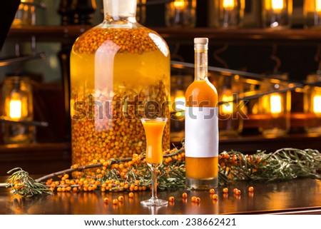 Homemade buckthorn liqueur in bottle on wooden table - stock photo