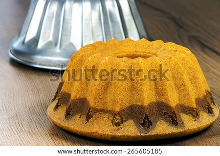 Homemade bundt cake with a form on a wooden table - stock photo