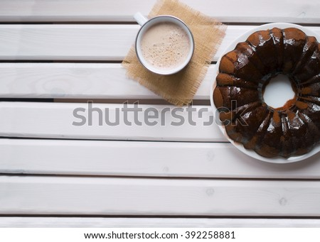 Homemade Bundt cake with chocolate icing, cup of hot coffee on a white wooden table. Top view. - stock photo