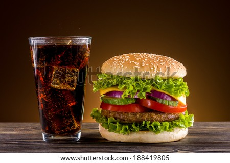 Homemade burger and coke on the wooden table - stock photo
