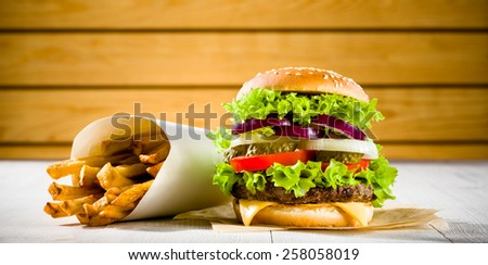Homemade burger and french fries on the wooden table - stock photo