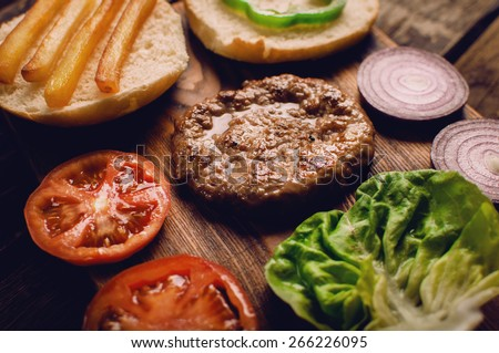 Homemade burger ingredients arranged on vintage wooden plate - stock photo