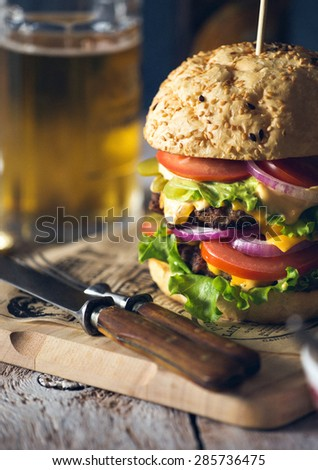 Homemade burger with a beef patty, cheese, fresh lettuce, onion and tomato on a fresh bun with sesame seed standing on a cutting board with glass of beer - stock photo