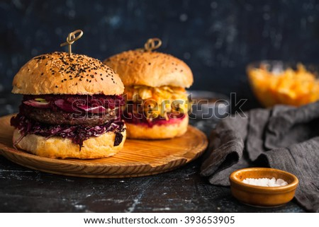 Homemade burger with bbq beef patties, red cabbage salad, beetroot dip and balsamic sauce served on small wooden chopping board over wooden table with black background. - stock photo