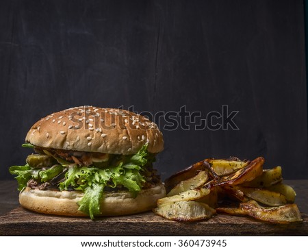 homemade burger with tuna, salad and fried potatoes with dill and garlic on a cutting board on wooden rustic background top view close up border, place for text  - stock photo