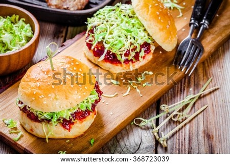 Homemade burgers with a cutlet of turkey, cranberry sauce and salad - stock photo