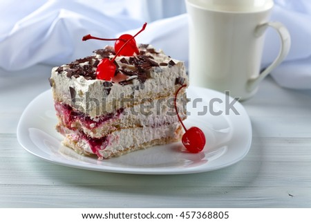 Homemade cake with cherries and chocolate on white plate - stock photo