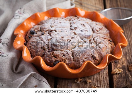 Homemade cake with raisins and walnuts in orange baking dish on a wooden table, selective focus - stock photo