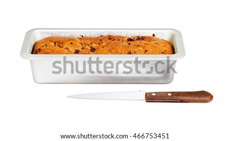 Homemade cake with raspberry chocolate in a rectangular metal mold for baking and knife isolated on white
