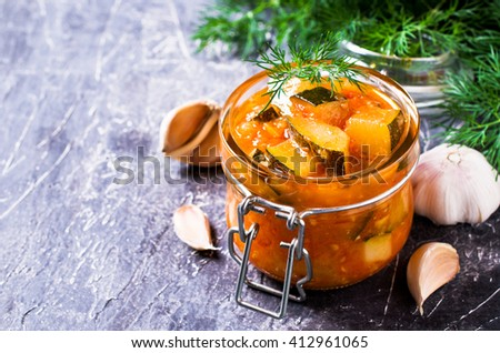 Homemade canned zucchini with vegetables in red sauce. Selective focus. - stock photo